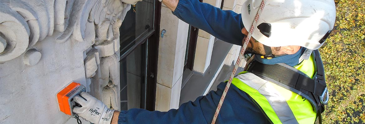 Building inspector abseiling on the outside of a building in London carrying out a Ground Penetrating Radar survey.