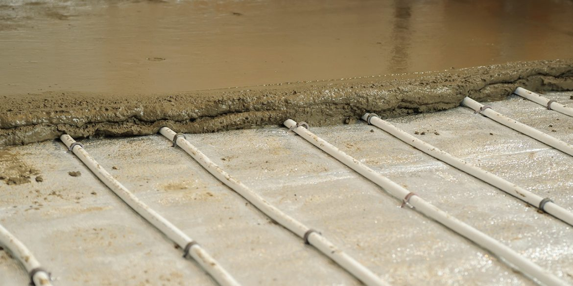 Underfloor heating pipes being covered with screed